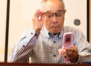 年金を携帯でチェックする高齢者