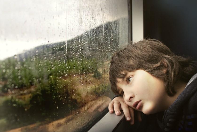 母親が嫌いな子供が窓際でぼーっとしている