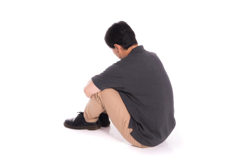 気にしすぎる人が座って落ち込んでいる