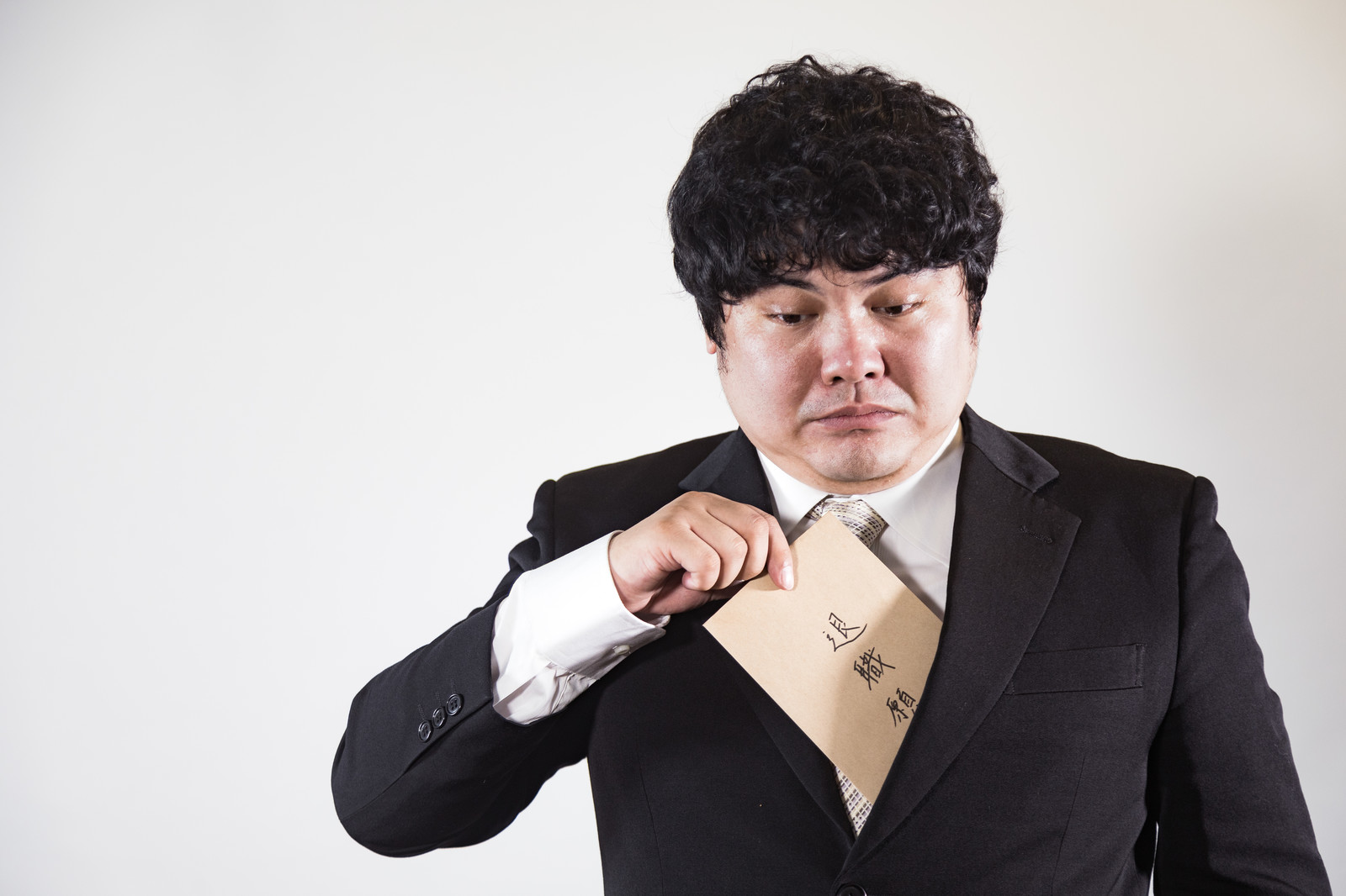 退職願を胸ポケットから出しているサラリーマン