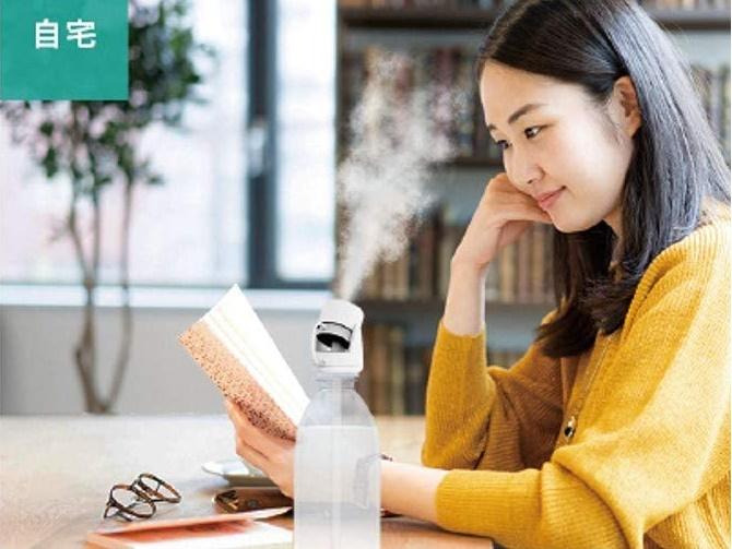 USBのペットボトル加湿器を使っている女性