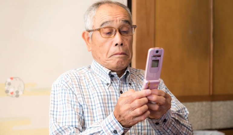 友人とメールをしている高齢者