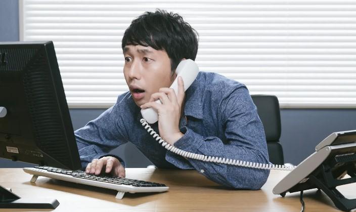 職場で緊張しながら電話に出ているサラリーマン